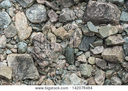 The background of grey rocks and boulders located on the bottom of the dry riverbed.