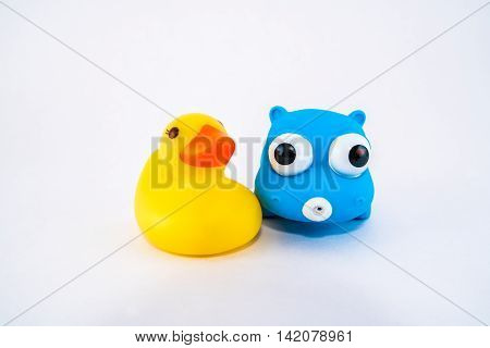 Yellow duck and blue hippo bath rubber clamping toys next to each other.