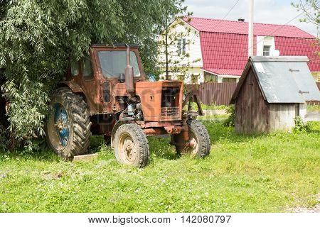 Old red rusty tractor near well on countryside