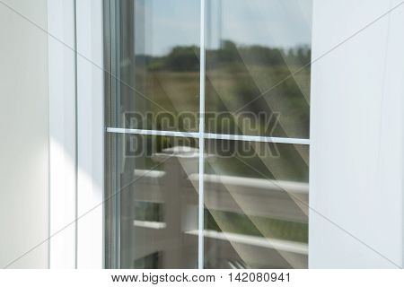 Plastic white window muntin bars with the reflection of the blue cloudy sky with green trees