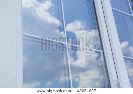 Plastic white window muntin bars with the reflection of the blue cloudy sky