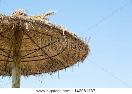 Grass parasol on a blue sky background