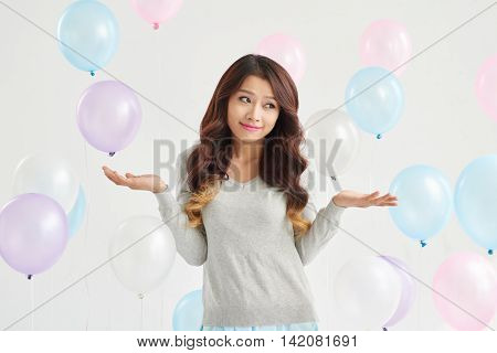 Portrait of confused young woman and balloons around her