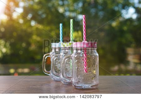 Three canning jars with colorful gingham lids. Selective focus.