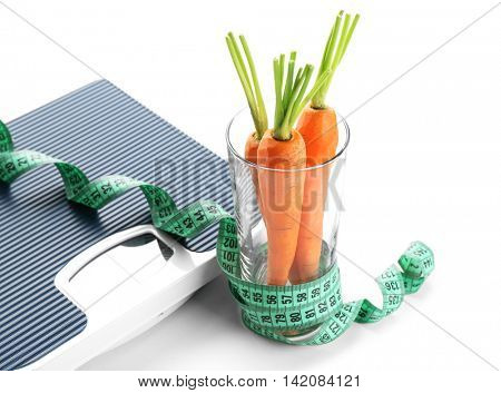 Bathroom scale with carrots on white background