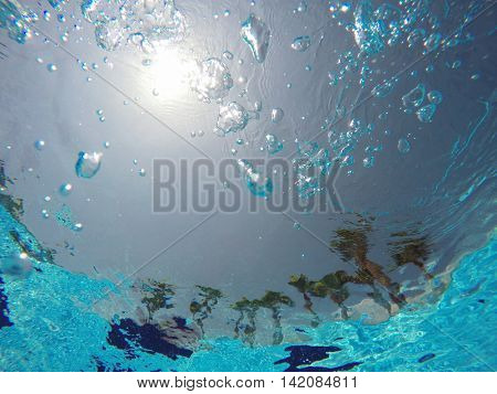 view of tropical beach through the pool water