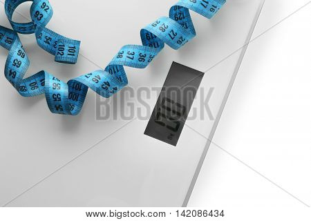 Bathroom scales with measuring tape, closeup. Weight loss concept