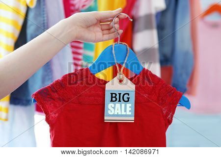 Female hand holding red clothes on hanger, closeup