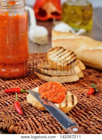 Relish (Ajvar) of Roasted Red Bell Peppers and Eggplants on toast slices.