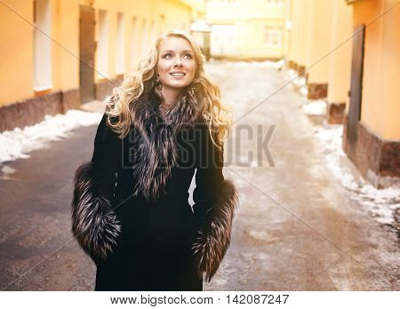 beautiful blond girl with long curly hair in fur coat close up street winter snowy portrait