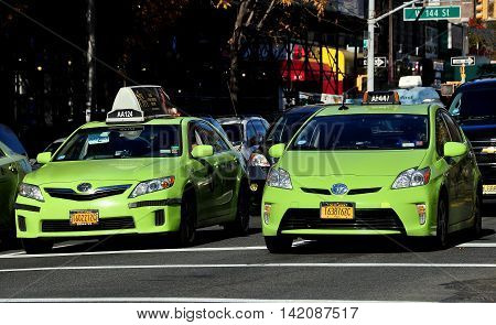 New York City - November 3 2015: Two NYC green Toyota taxis waiting at a traffic light on Broadway in Hamilton Heights