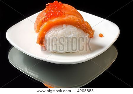 Sushi with salmon and caviar on a white plate and black background with reflection