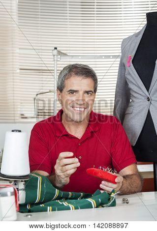 Happy Fashion Designer Sitting At Workbench