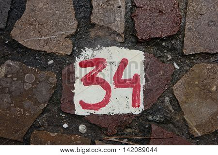 The number 34 painted with red paint on white background on wall of stone masonry