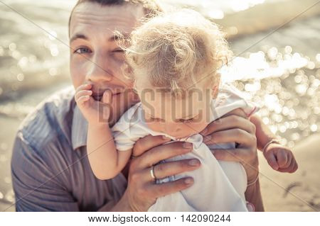 Dad and daughter together on the beach coast during holidays with shining sea on background. Father embrace child. Soft focus on father face