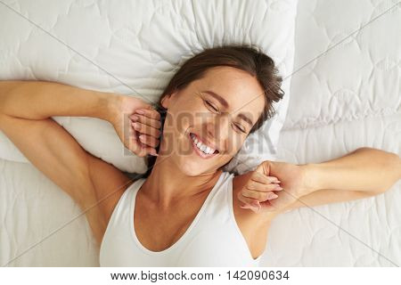 Young beautiful woman waking up in her bed fully rested. Woman stretching in bed after awakening