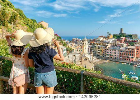 Two girls tourists admiring Vernazza. Cinque Terre National Park. Liguria. Italy.