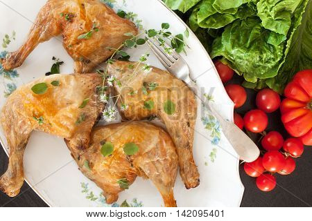Top view of plate with roasted chicken legs flavored with fresh marjoram.