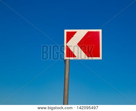 Small red traffic sign against a blue sky in the daytime