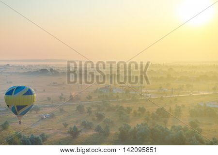 Hot air balloon is flying over morning summer foggy landscape. Romantic journey