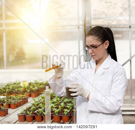 Young woman biologist in white coat holding test tube with orange liquid over flower pots in greenhouse