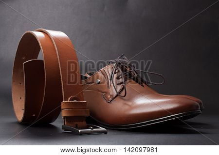 Selective Focus Of Men's Leather Belt And Shoe On Wooden Table
