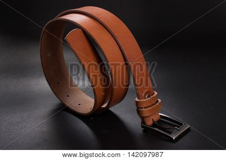 Man's belt on black background fashion concept