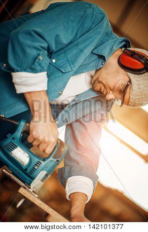 Carpenter at work.Man cutting wood plank using electric jig saw.