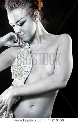 The Girl With A Silver Skin Poses On A Black Background