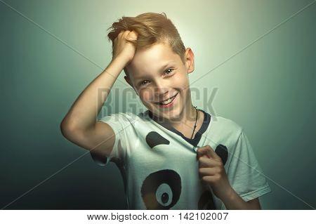 Portrait of happy joyful beautiful teenage boy with stylish haircut and bright eyes softbox lighting studio shot.