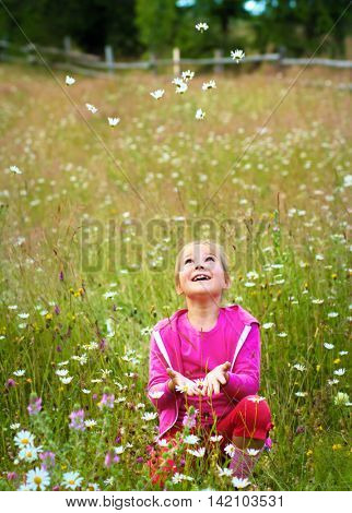 Girl is throwing daisies up, outdoor shoot