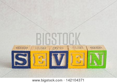 The word seven (7) spelled with colorful alphabet blocks isolated against a white background