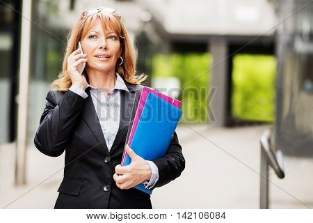 Businesswoman on the phone outdoors.Mature businesswoman with a folder at the office building.