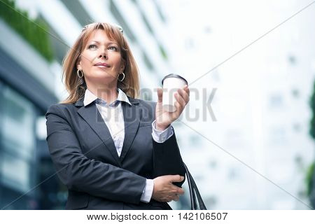 Businesswoman standing in front of an office building.She is drinking take-away coffee.