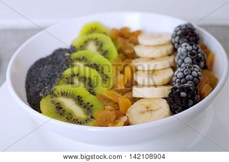 Kiwi banana dewberry raisin oatmeal smoothie bowl. Healthy eating breakfast.