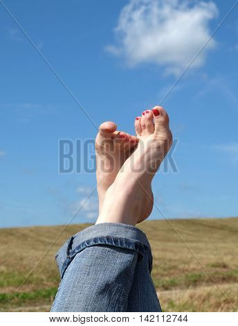 Beautiful playful female bare feet with red nails in rolled blue jeans close-up against summer nature landscape with meadow and blue sky with clouds vertical view