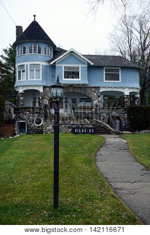 WEQUETONSING, MICHIGAN / UNITED STATES - DECEMBER 22, 2015: A lamppost, with an attached sign indicating the house number and owner's name, stands in front of a large blue mansion on Beach Road in Wequetonsing.