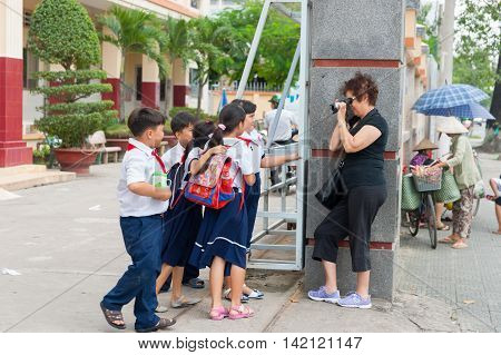 Can Tho, Vietnam - October 15, 2013; Group of uniformed students willingly pose for tourist to photograph them in city street