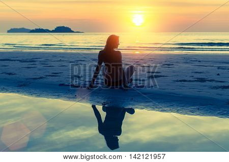 Silhouette of young beautiful girl sitting on the beach during sunset.