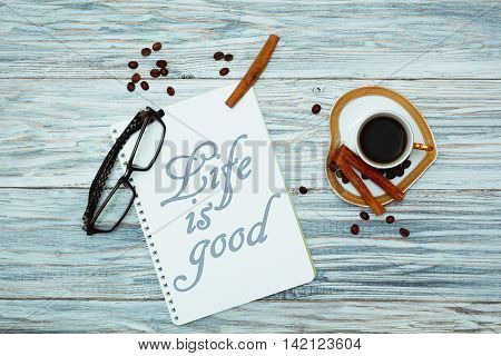 Morning coffee and text in notepad: Life is good. Flat lay