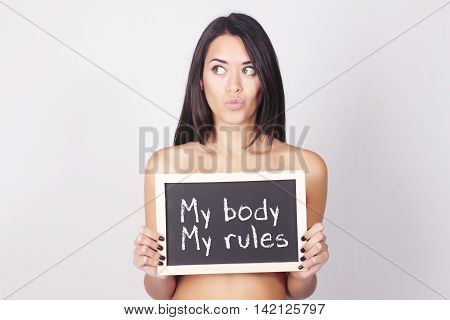 Young beautiful woman holding a chalkboard saying My body my rules. Women power concept.