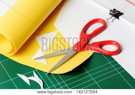 cutting paper with red scissors, closeup scissors