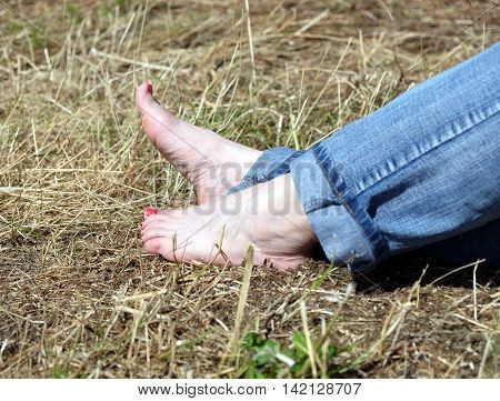 Barefoot female feet in rolled blue jeans resting on dry hay and takes sunbath in sunny day side view close-up with focus on feet