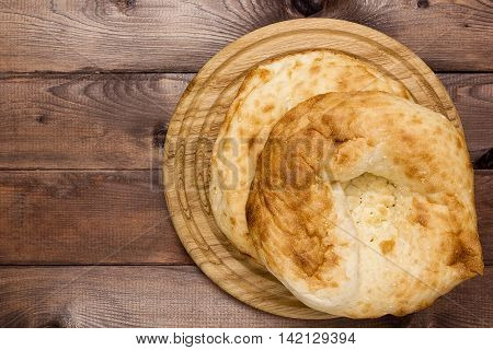 Traditional Uzbek bread on a plate on a wooden background