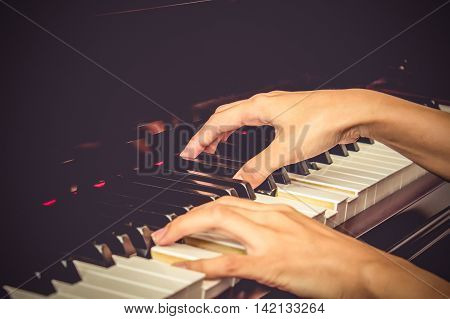 Close up of young girls hands playing piano. vintage tone filter effected