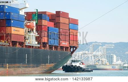 Oakland CA - July 27 2016: Tugboat Veteran at the stern of Cargo Ship APL TOURMALINE assisting the vessel to maneuver into the Port of Oakland the fifth busiest port in the U.S.