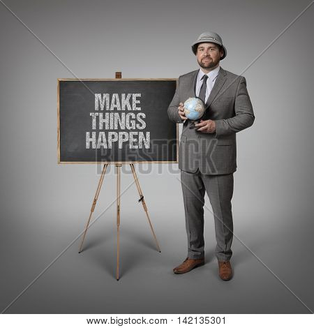 Make things happen text on blackboard with businessman holding globe in hands