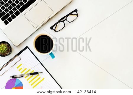 White office desk table with eyeglasses chart or graph over backboard pen laptop and cup of coffee. Top view with copy space