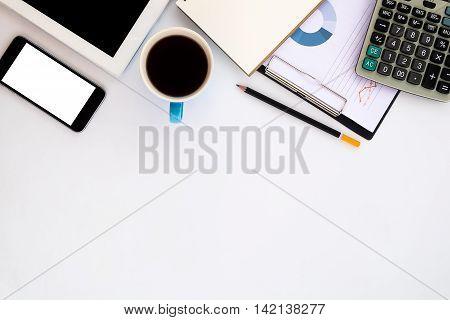 White office desk table with tablet pencil calculator cup of coffeeblank screen smartphoneleather notebook and graph or chart.Top view with copy space.Business desk table concept.
