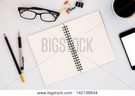 White office desk table with empty page leather notebookpenpencileyeglassesblank screen smartphone and cup of coffee. View from above.Business desk table concept.Office supplies and gadgets on desk table.Flat lay photo.